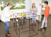 Eliane Niederberger, Petra Müller und Michel von Känel (von links) bauen mittels elastischer Bänder anspruchsvolle Figuren in einem riesigen Würfel.