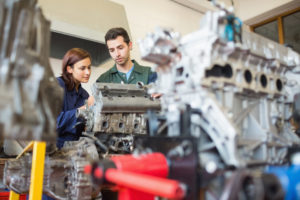 Calm trainee and instructor repairing an engine
